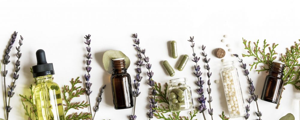 Homeopathy eco alternative medicine concept - classical homeopathy pills, thuja, eucalyptus, lavender essential and aroma oil and healing herbs and on white background. Flatlay. Top view. Copyspace